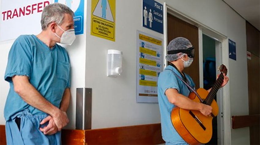 A hospital worker listens as Coss entertains staff and patients.