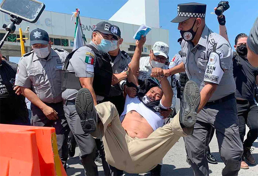 Security forces arrest a protester at the toll plaza on Thursday.