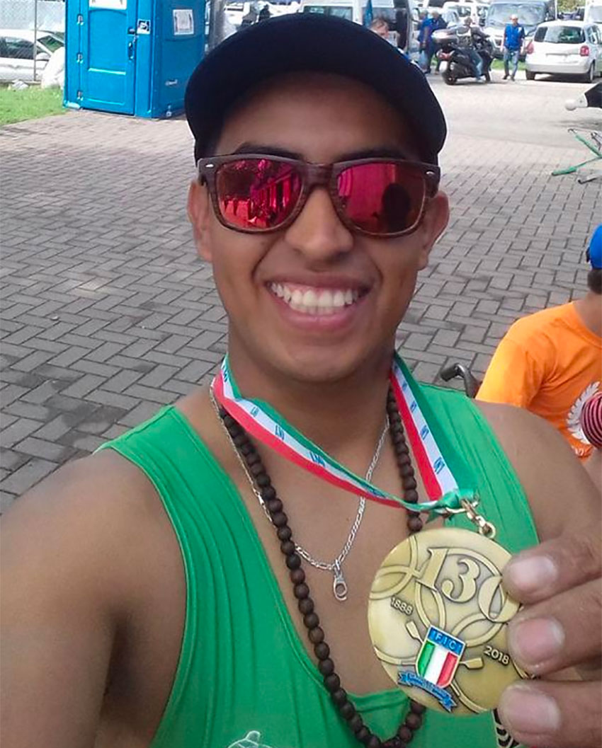 Ramírez shows off a rowing medal.