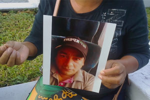 Andrade with a photo of her late husband, whose body was mistaken for that of another virus victim.