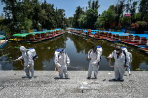 Workers disinfect a walkway in Xochimilco, Mexico City.