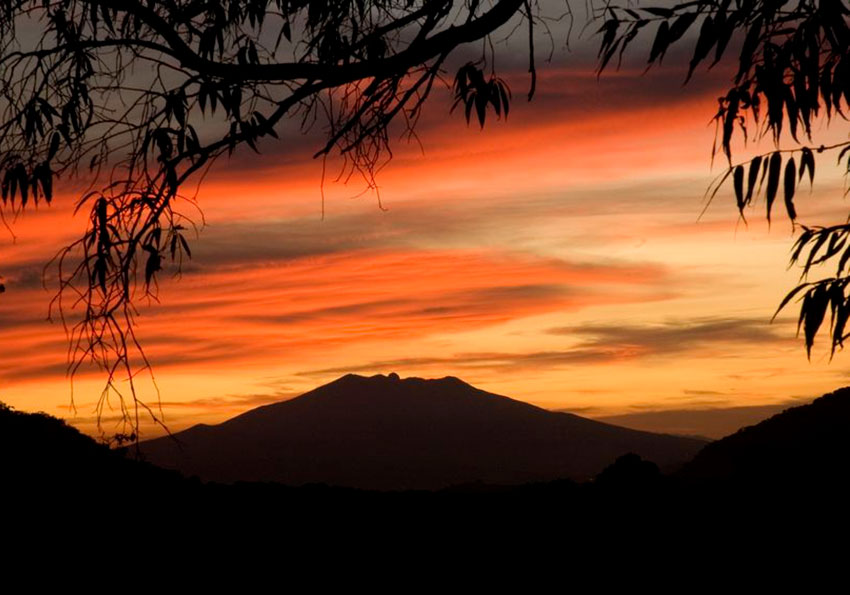 The sun sets behind Tequila Volcano.