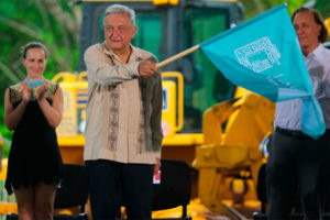 The president waves the starter's flag at inauguration of construction of the Maya Train in June.