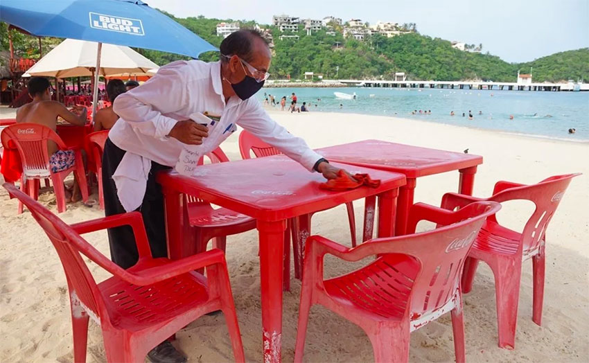 A waiter prepares a table at one of Huatulco's beaches.