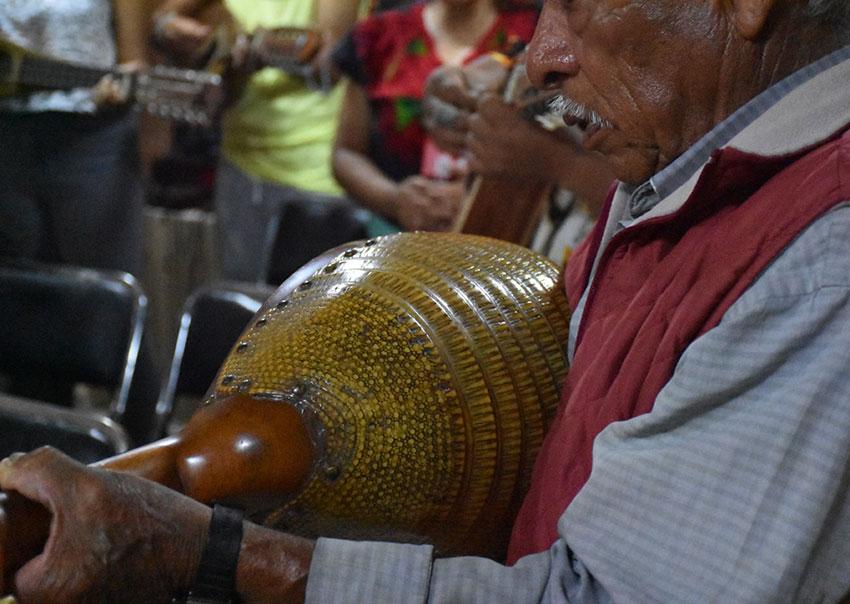 Un conchero sosteniendo un instrumento de cuerda llamado concha