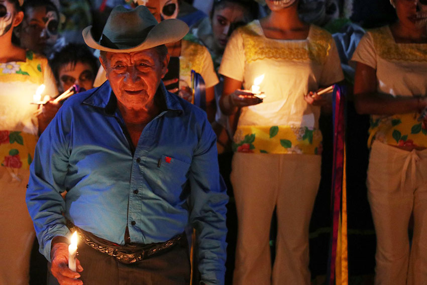 A man carries a candle at a Festival of the Souls in Quintana Roo