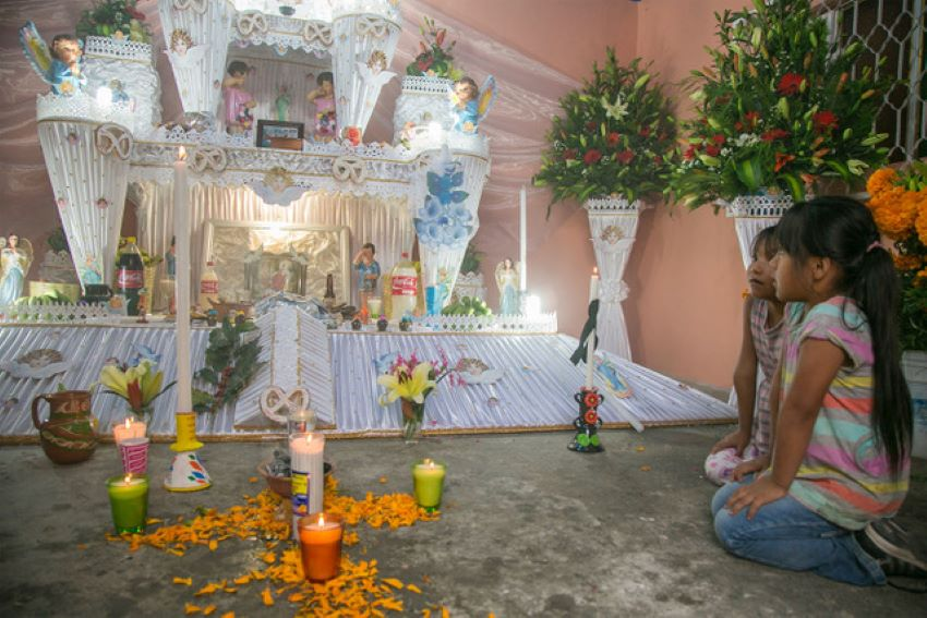 Girls at a rare three-tiered memorial altar in Huaquechula, Puebla.
