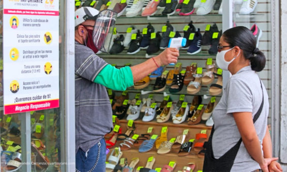 A customer's temperature is checked at a store in Guadalajara in July.