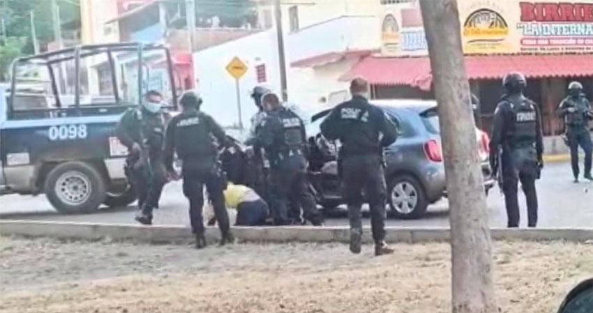 Police haul woman from her car in Culiacán on Thursday.