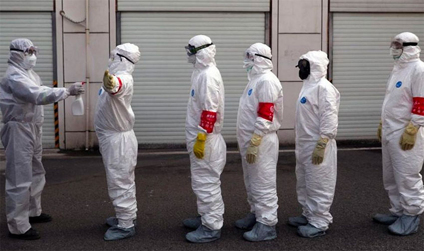 Healthcare workers line up for Covid disinfection.