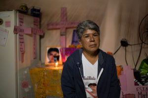 Lidia Florencio sits in front of the altar she put out for her daughter in her home.