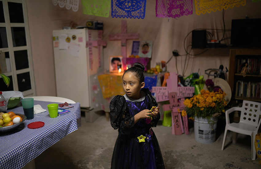 Lidia's youngest daughter Camila, 6, in front of an altar