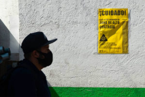 A man walks by a sign in Mexico city warning that the area is high risk for Covid contagion.