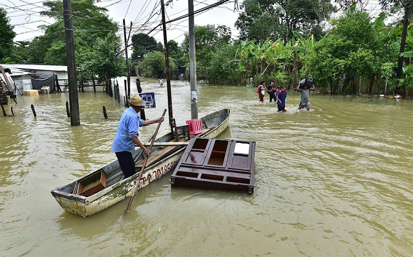 A man attempts to save a piece of furniture on a flooded road in Tabasco.