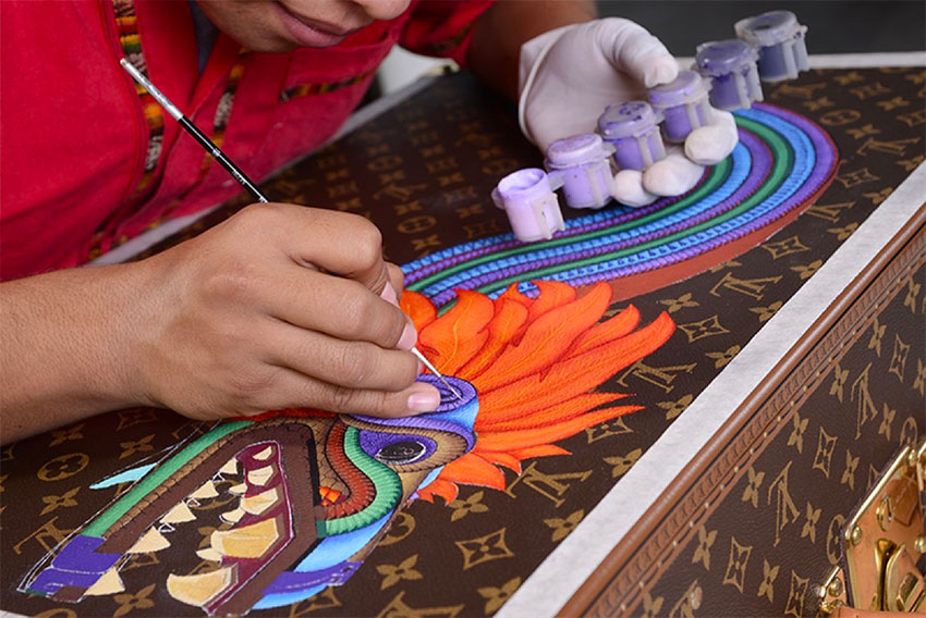 A Zapotec artist at work on a Vuitton trunk.