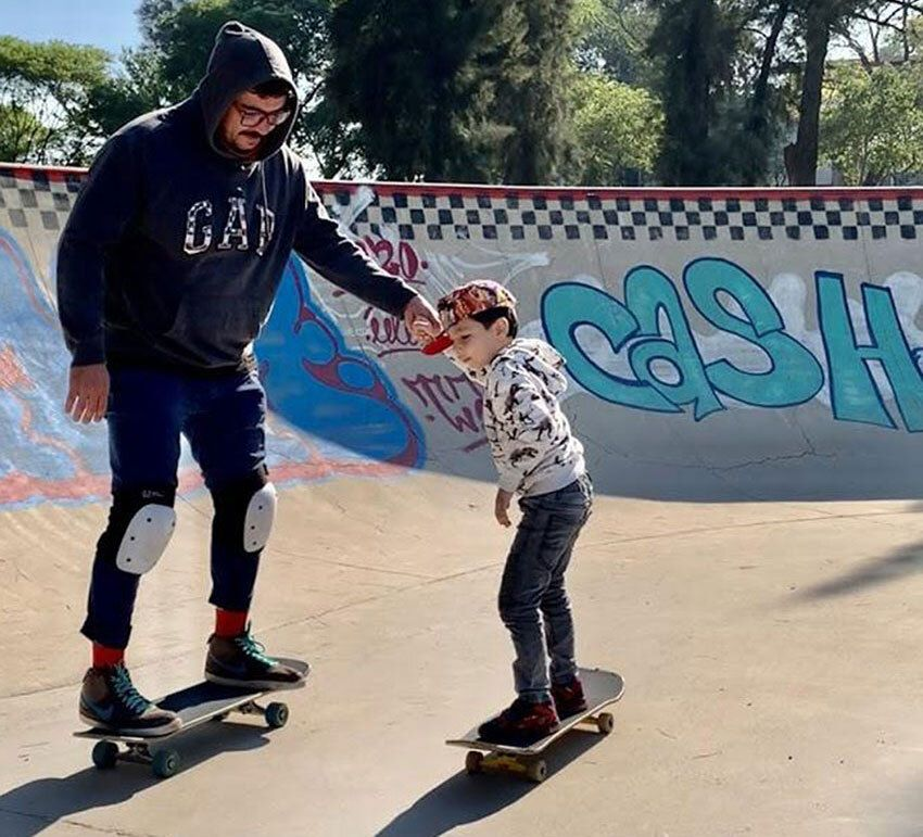 A frequent sight at skateparks: a father teaches his son to skate.