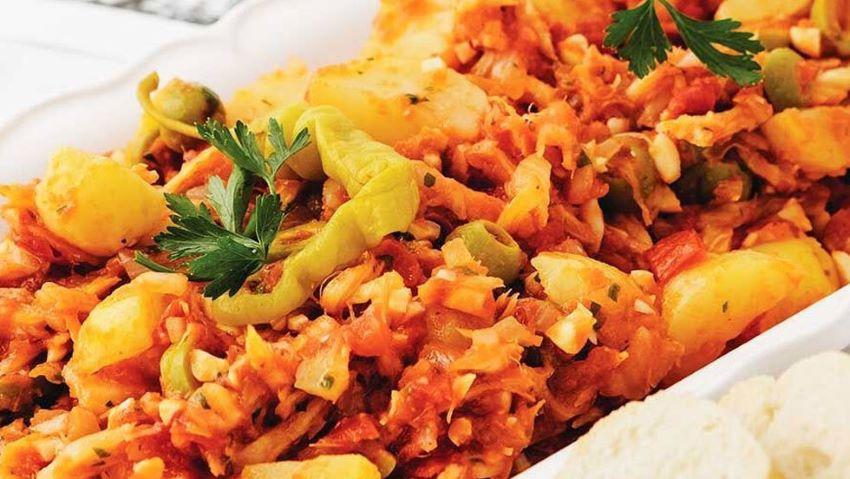 Las aceitunas verdes y alcaparras españolas de Bacalao traicionan las raíces coloniales del plato.