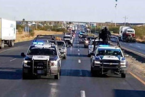 Police escort the caravan of Mexicans returning home for the holidays.