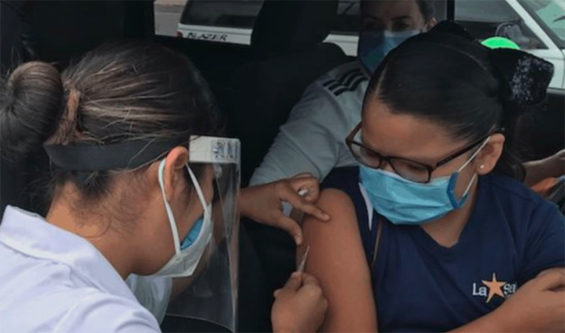 A healthcare worker administers a flu shot to a passenger in a car in Chihuahua.