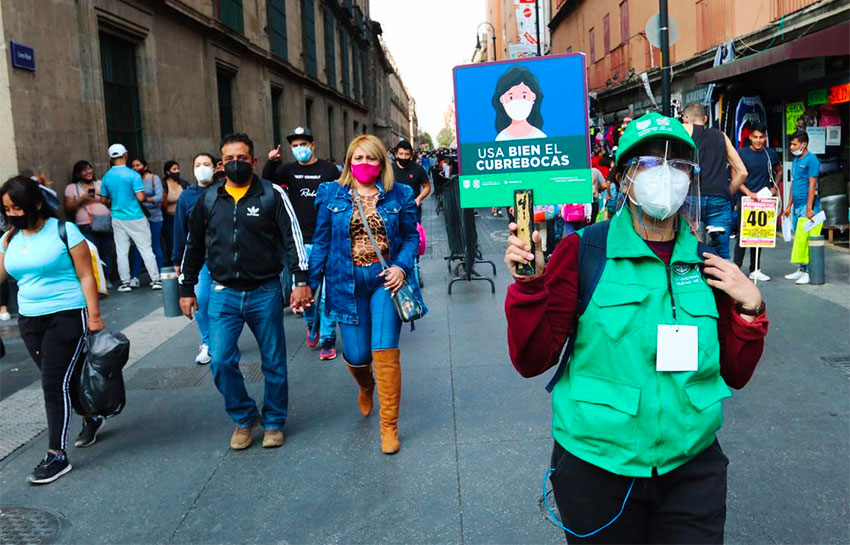 A Mexico City worker displays a sign urging the correct use of face masks.