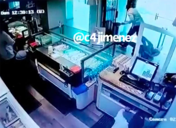 Employees crouch behind the counter as the theft takes place outside the ice cream parlor.
