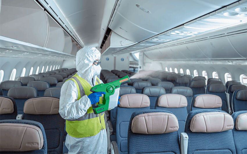 An airline employee sanitizes an airplane before boarding.