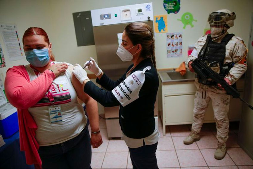 armed guard watches over the vaccination of healthcare workers.