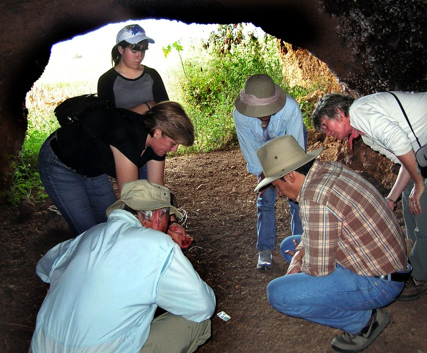 Visitors examine shards on the floor of one of the island's caves.