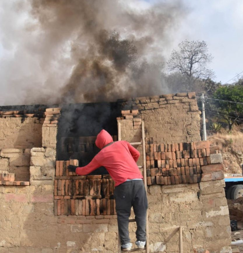 Gabino Noselo's grandson, Adolfo, seals the oven's door with unfired bricks.