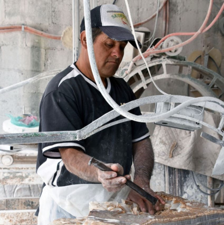 Francisco Camargo works on a marble slab.