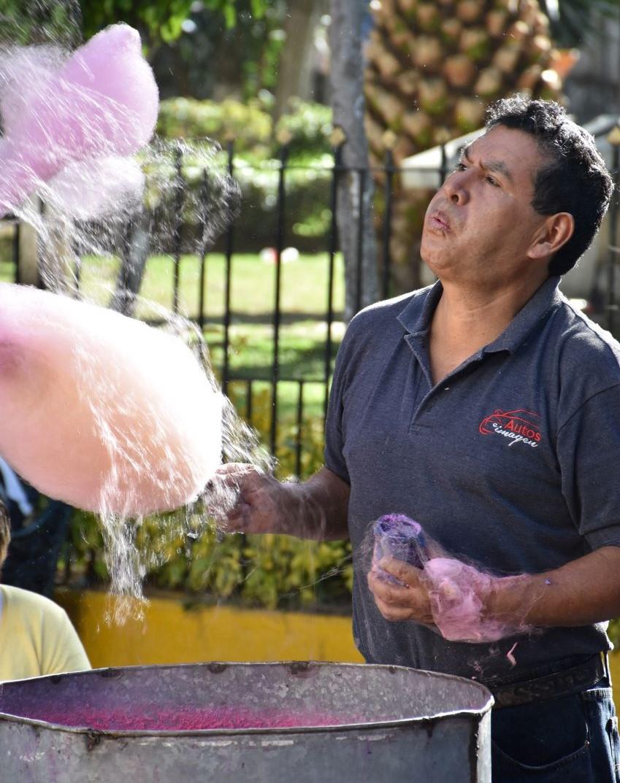 San Gregorio Atlapulco vendor blowing cotton candy wisps into the air.