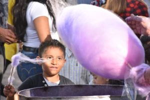 A boy watching a cotton candy vendor captures wisps of floating sugar on his stick.