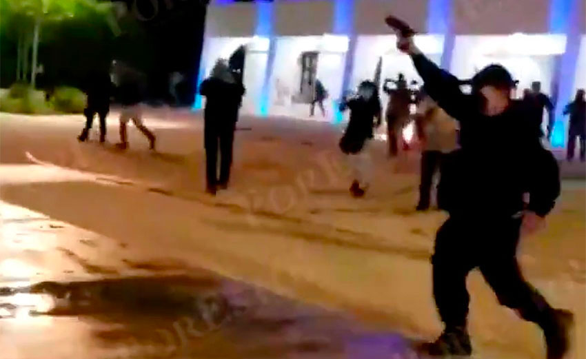 An officer fires his weapon during a protest last year in Cancún.