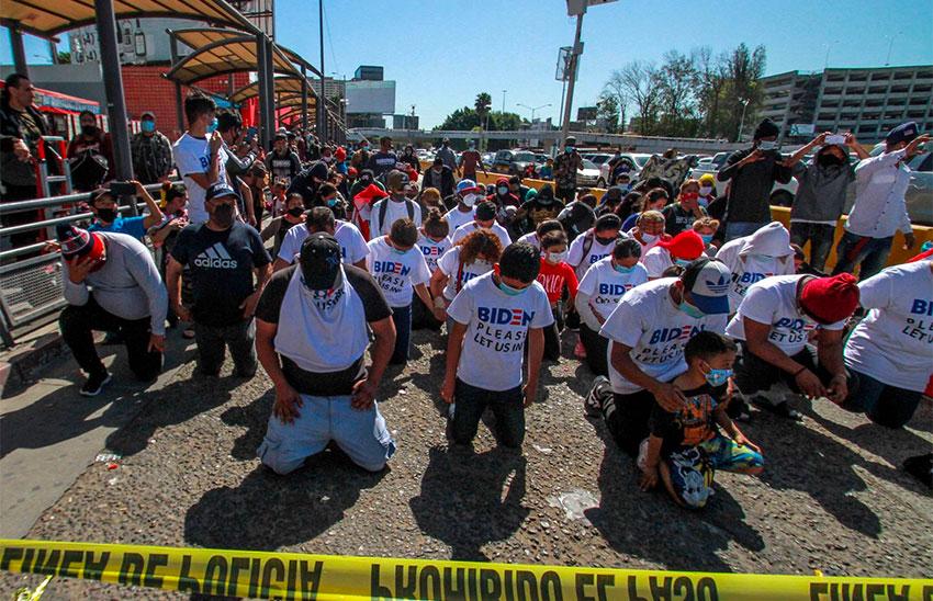 Migrants in Tijuana kneel at the border