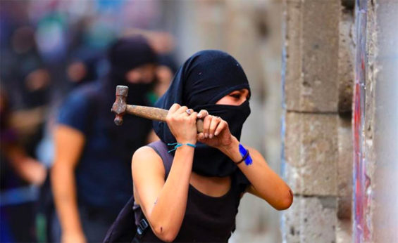 A protester takes a hammer to barricades at the National Palace last week.