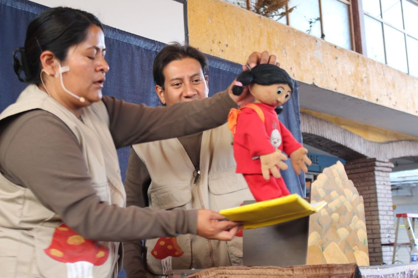 """Reyes and Ledesma on stage with a puppet. The two do not hide themselves during performances, but Reyes says that they """"melt"""" into the background."""