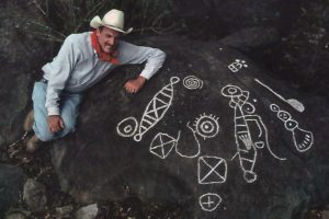 Archaeologist Joseph Mountjoy with examples of Huichol petroglyphs he, with help from National Geographic, documented for exhibit at the Casa Cultura in Mascota.