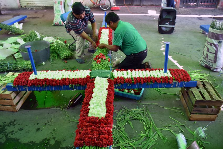 Decorating a cross in preparation for the feast day.