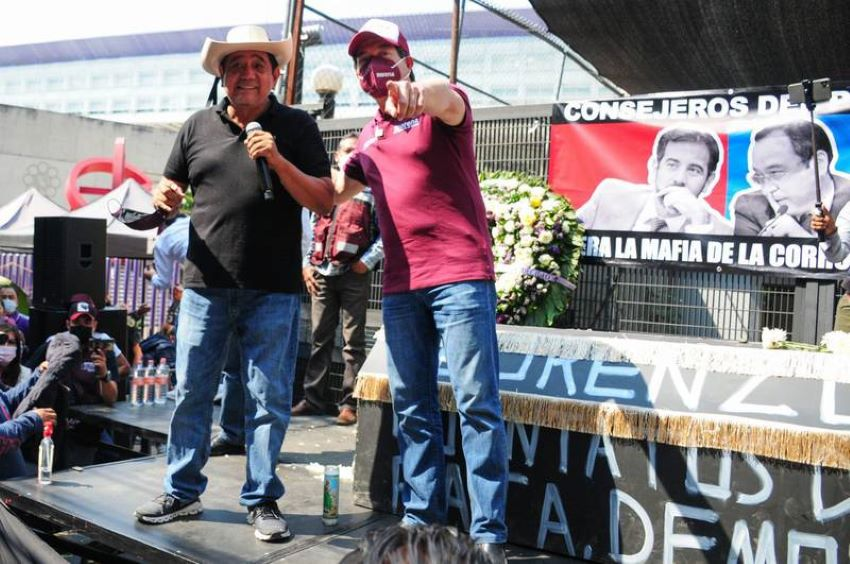 Salgado (l) at the protest with Morena Party president Mario Delgado. In the background, a banner accuses the INE's councilors of corruption.