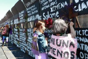 Women in Mexico City writing femicide victims' names onto metal barriers authorities had installed in anticipation of International Women's Day.
