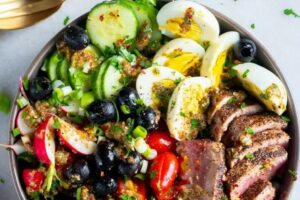Hard-boiled eggs and tomatoes lend a dash of color to this hearty Nicoise Salad.
