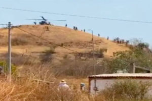An army helicopter delivers supplies to soldiers camped outside the city of Aguililla.