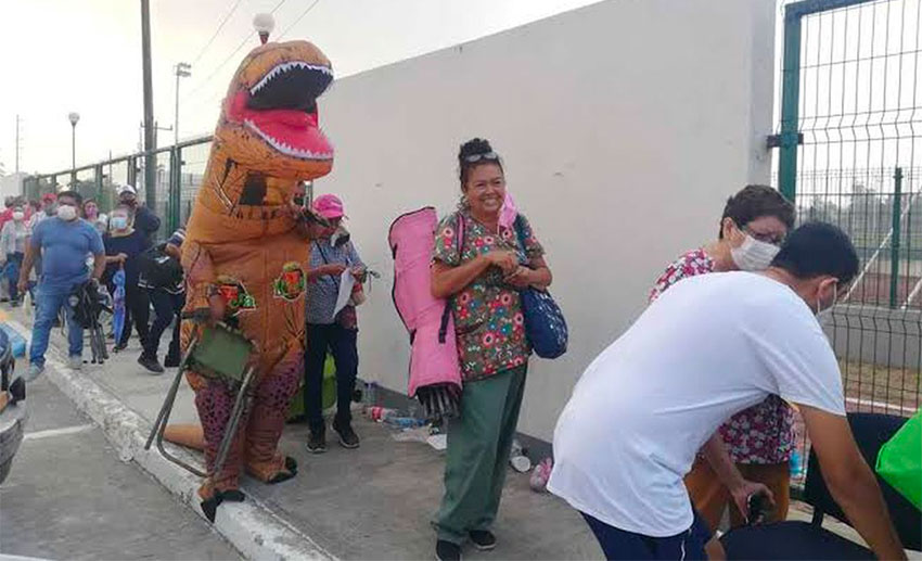 The dinosaur's mom looks decidedly cheerful despite having to wait in line.