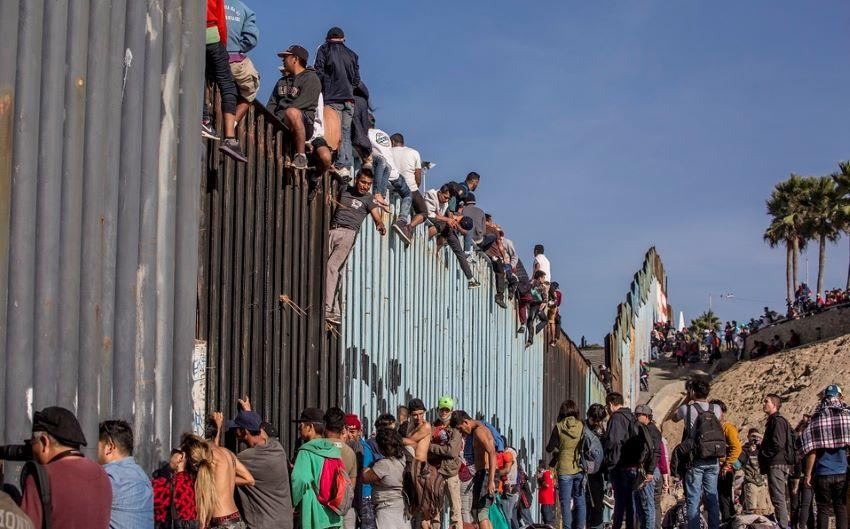 Migrants at the Mexico-US border wall.