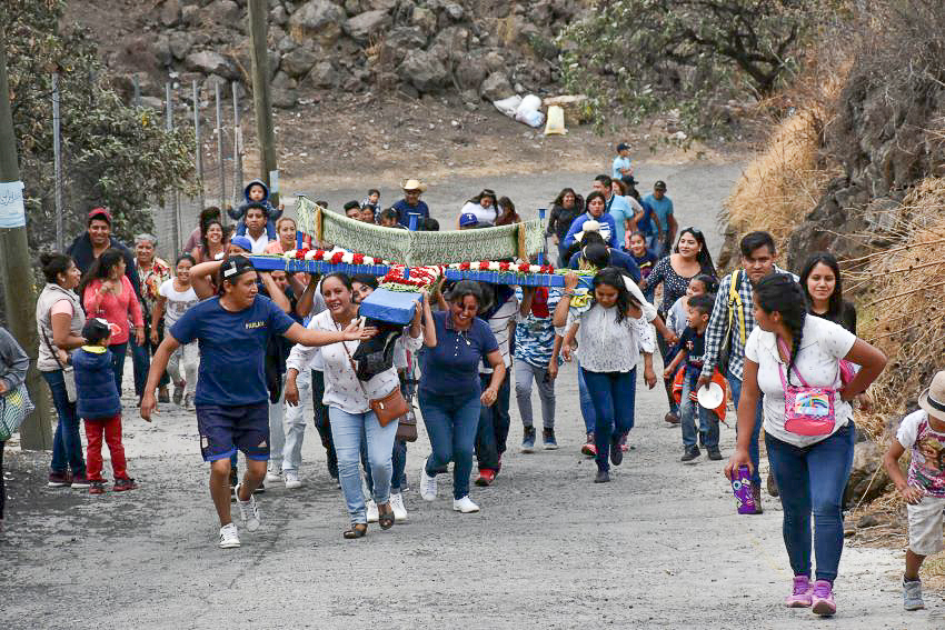 While maintaining the crosses on a hill above San Gregorio Atlapulco is a solemn duty, the women entrusted with bringing it uphill do the work with joy and laughter.