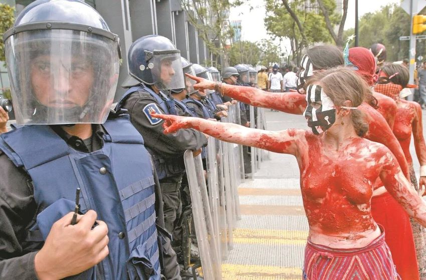 Feminist protesters in an unrelated demonstration face off against the National Guard.