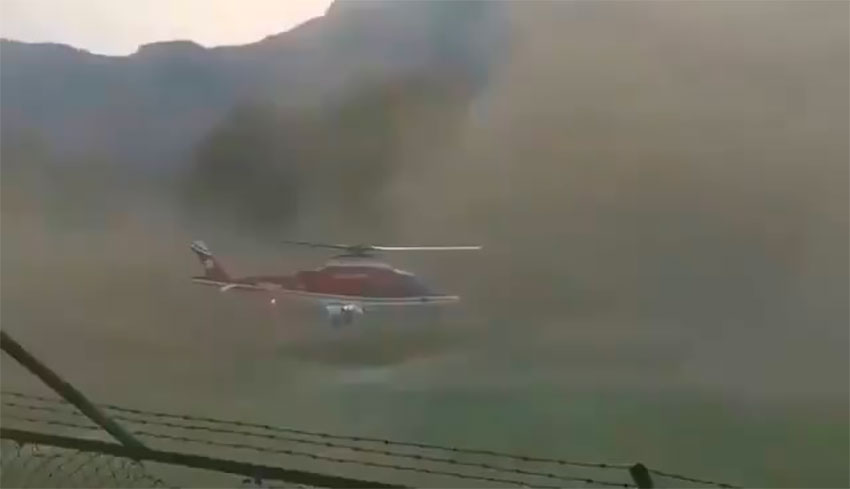 The helicopter amid a huge cloud of dust.