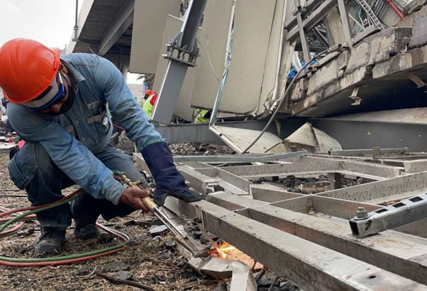 A worker removes debris from the Metro Line 12 accident site.