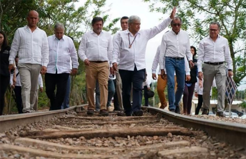 López Obrador walks a section of old railway on the route of the Maya Train.