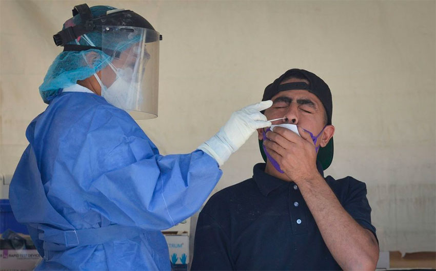 A healthcare worker administers a Covid test.